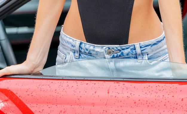 청바지와 빨간 차 소녀입니다. 현대적인 트렌디한 유스 스타일.