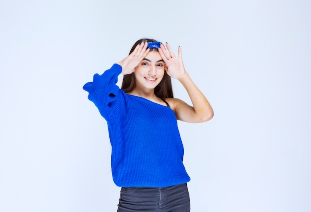 彼女は混乱して驚いて頭を抱えている青いパーティードレスの女の子。