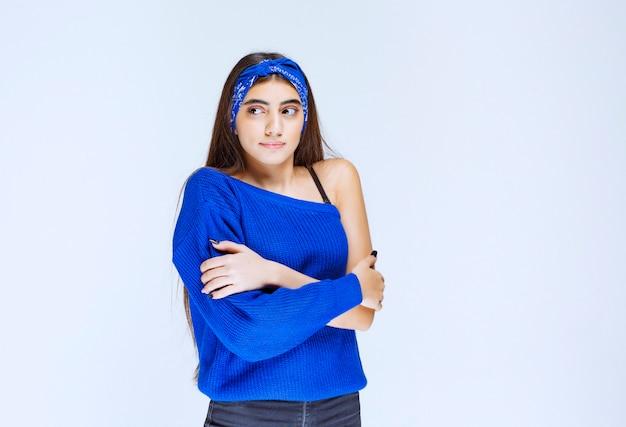 寒さを感じている青いパーティー衣装の女の子。