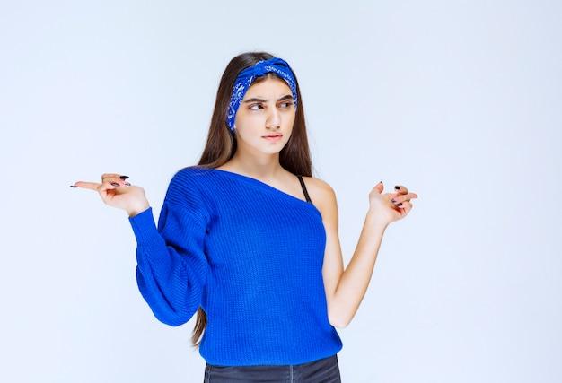 뭔가 주위를 가리키는 파란색 파티 셔츠에 소녀.