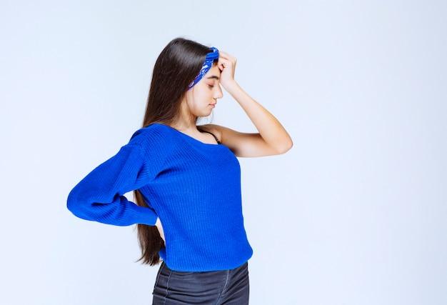 眠そうな青いシャツを着た女の子。