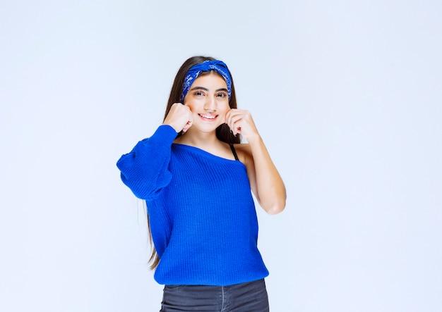 매혹적이고 쾌활한 포즈를 취하는 파란색 셔츠를 입은 소녀.