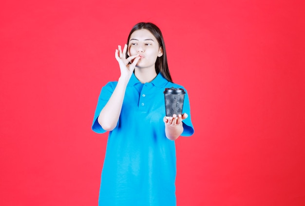 Девушка в голубой рубашке держит черную одноразовую кофейную чашку и наслаждается вкусом.