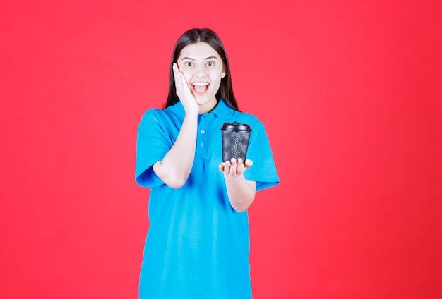 黒の使い捨てコーヒーカップを保持し、前向きに感じている青いシャツの女の子
