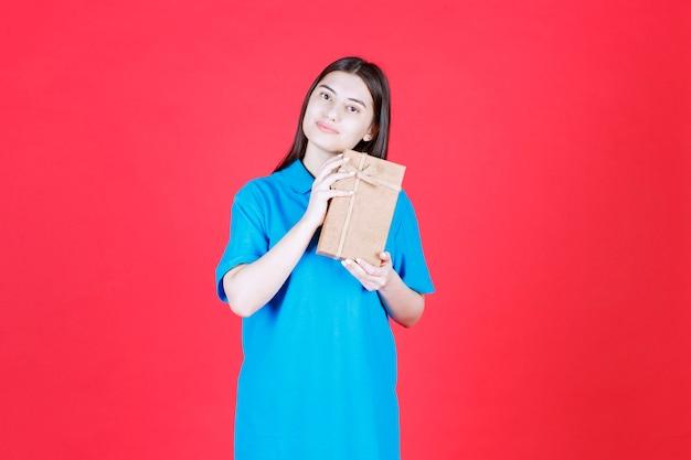 Девушка в голубой рубашке держит картонную мини-подарочную коробку и выглядит смущенной.