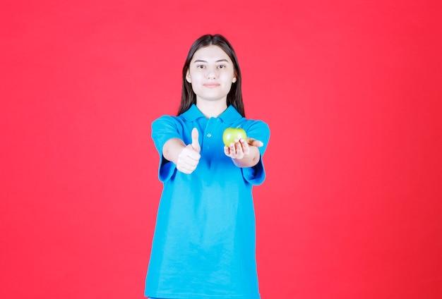 Девушка в синей рубашке держит зеленое яблоко и показывает знак рукой
