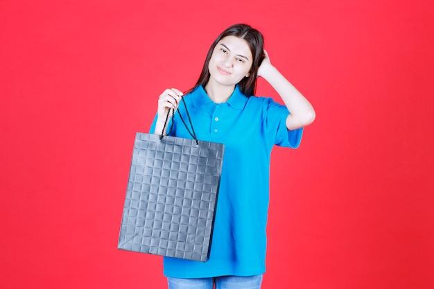 Девушка в синей рубашке держит фиолетовую сумку для покупок и выглядит смущенной и задумчивой