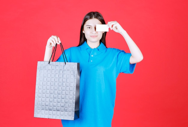 Девушка в синей рубашке держит фиолетовую сумку для покупок и представляет свою визитную карточку