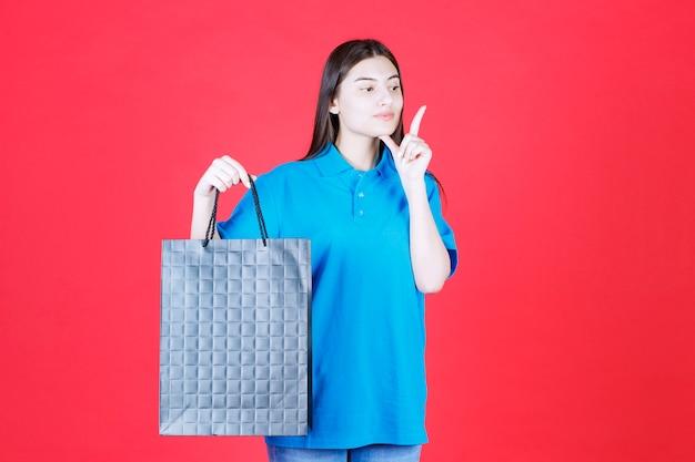 Девушка в синей рубашке держит фиолетовую сумку для покупок