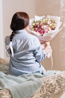큰 분홍색 장미 꽃다발을 들고 침대에서 즐기는 파란색 셔츠를 입은 소녀