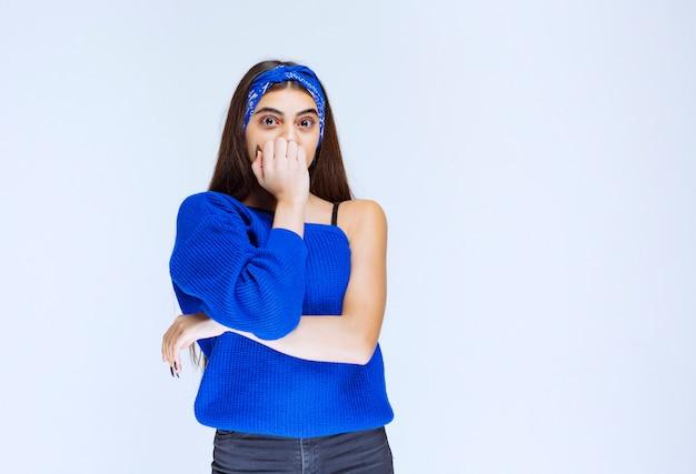 Девушка в синей рубашке выглядит напуганной и напуганной.