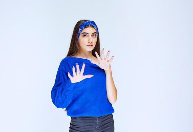 青いシャツを着た女の子は怖くて怖がっているように見えます。