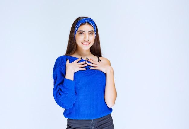 Девушка в голубой рубашке, указывая на себя.