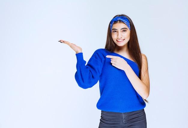 Девушка в голубой рубашке, указывая на левую сторону.