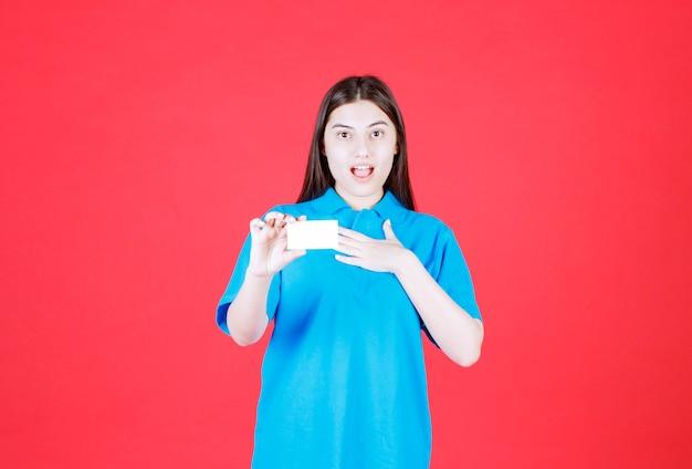 Девушка в синей рубашке, представляя свою визитную карточку и указывая на себя