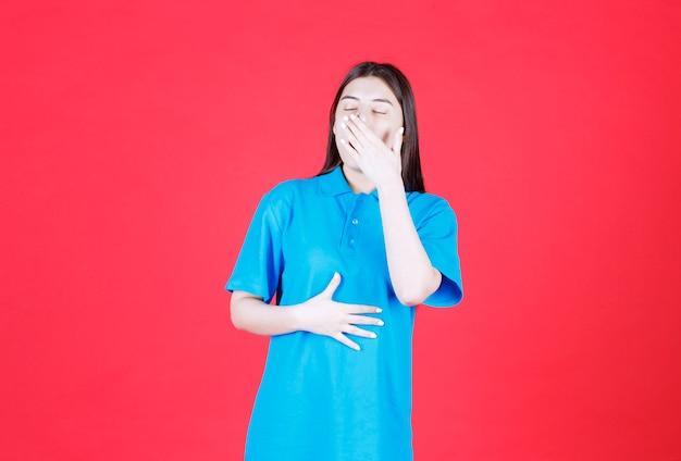 파란 셔츠를 입은 소녀는 빨간 벽에 서서 악취 때문에 숨을 참습니다.