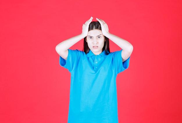 赤い壁に立っている青いシャツを着た女の子は、怖くて怖がっているように見えます。