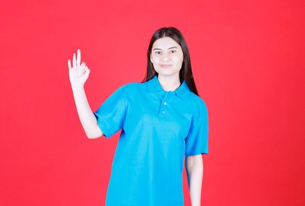 Девушка в синей рубашке стоит на красной стене и показывает положительный знак рукой