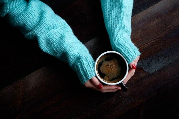 コーヒーのカップの手のクローズアップを保持している青いセーターの女の子