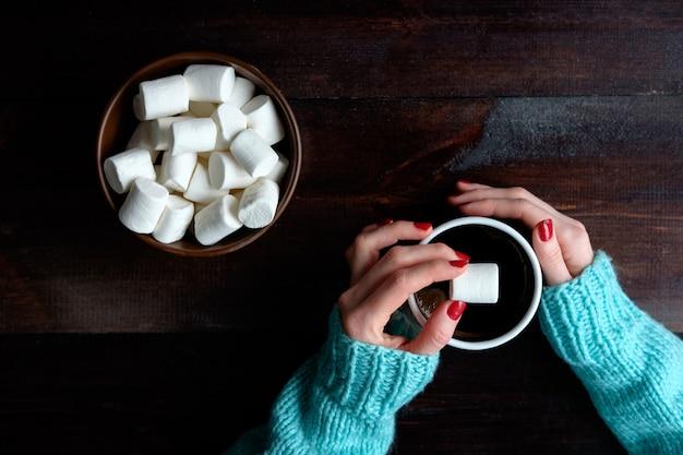 コーヒーのカップを保持している青いセーターの女の子手マシュマロコピースペースのクローズアップボウル