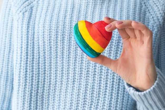 Девушка в синем свитере, держа в руке сердце лгбт, гомосексуальную любовь.
