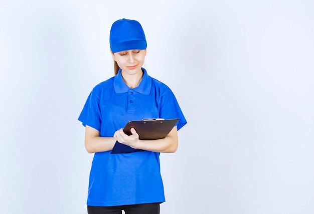 Девушка в синей форме держит папку с черным отчетом.