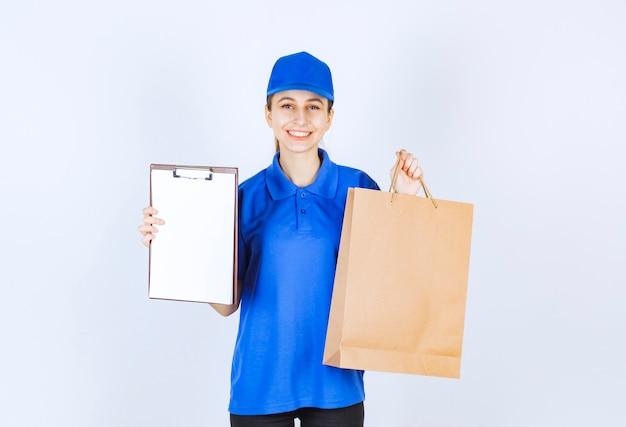 Девушка в синей форме держит картонную хозяйственную сумку и список клиентов.