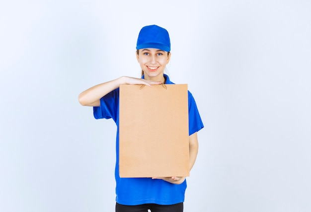 段ボールの買い物袋を保持している青い制服を着た女の子。