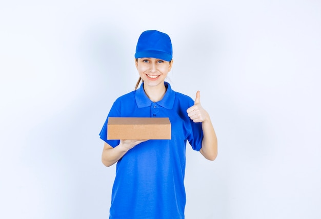Девушка в синей форме держит картонную коробку на вынос и показывает знак удовольствия.