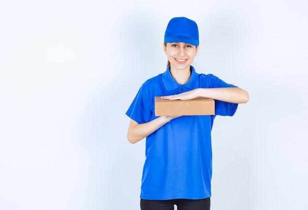 Девушка в синей форме держит картонную коробку на вынос.