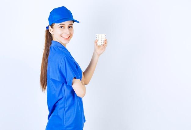 Девушка в синей форме держит чашку напитка.
