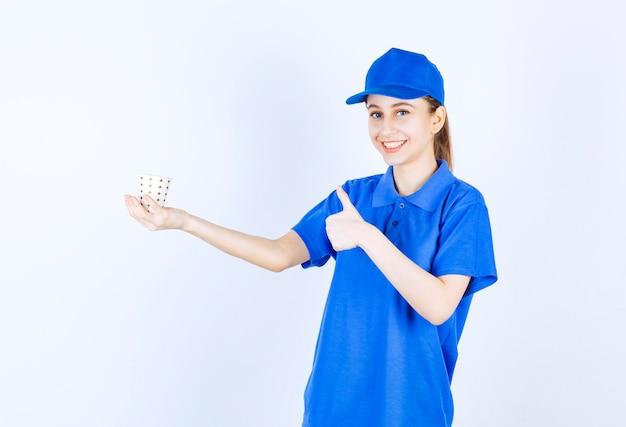 Девушка в синей форме держит одноразовую чашку напитка и показывает знак удовольствия.