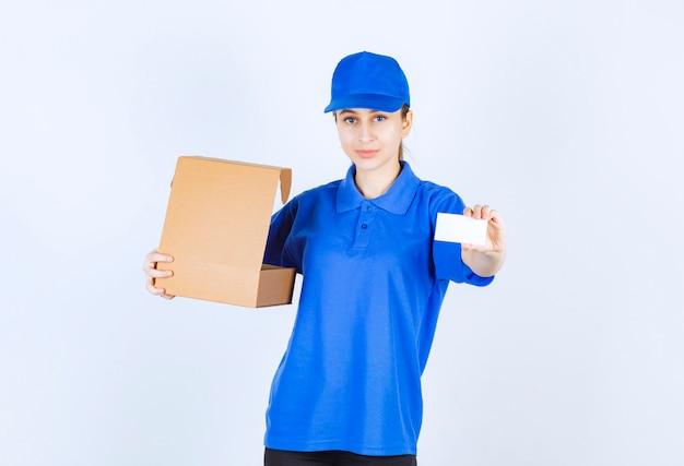 Девушка в синей форме держит открытую картонную коробку на вынос и представляет свою визитную карточку.