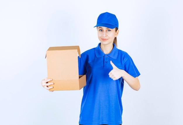 Девушка в синей форме держит открытую картонную коробку на вынос и показывает знак рукой удовольствия.