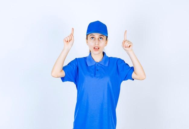 上の何かを指している青い制服を着た女の子。