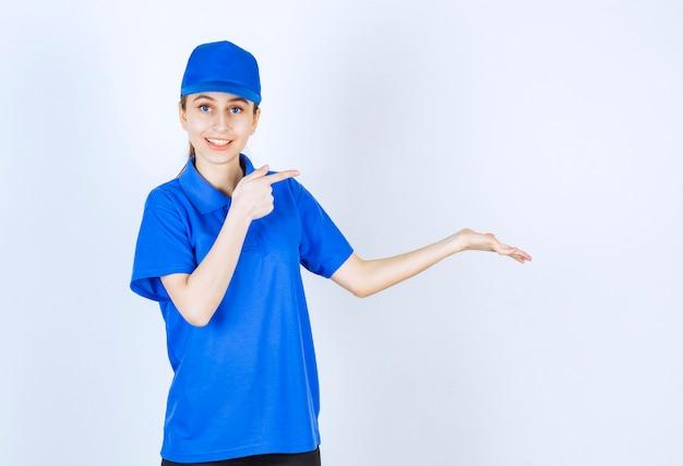 Девушка в синей форме указывает на что-то справа.
