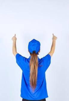 後ろ向きに見える青い制服を着た女の子。