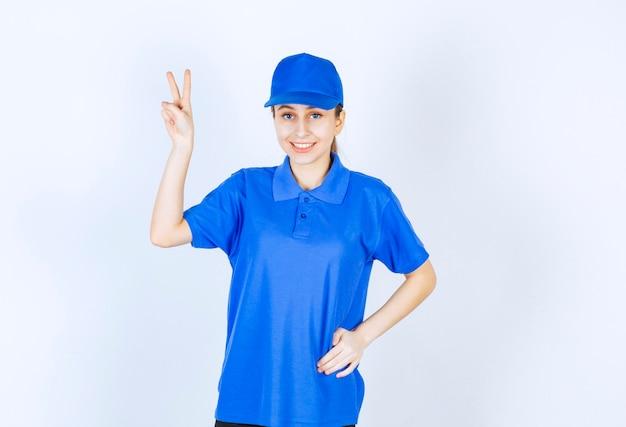 楽しさのサインを示す青い制服を着た女の子。