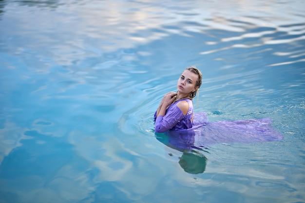 ボディコンドレスの女の子が湖で浴びる