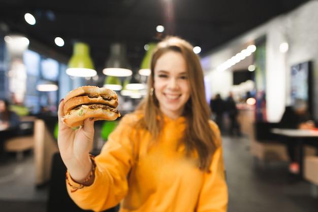 Девушка в яркой одежде держит аппетитный большой гамбургер на фоне ресторана быстрого питания