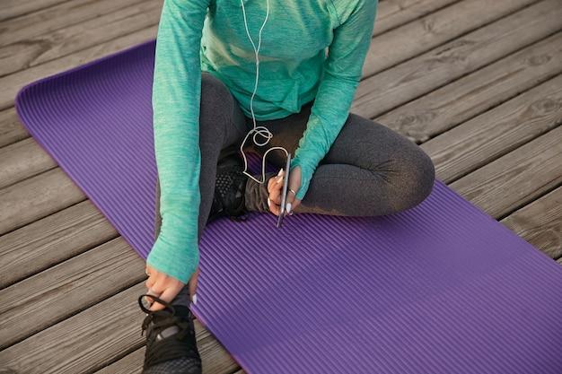 明るいスポーツウェアの女の子は、スマートフォンを持って、朝の練習の後に休憩し、紫色のヨガマットに座っています。
