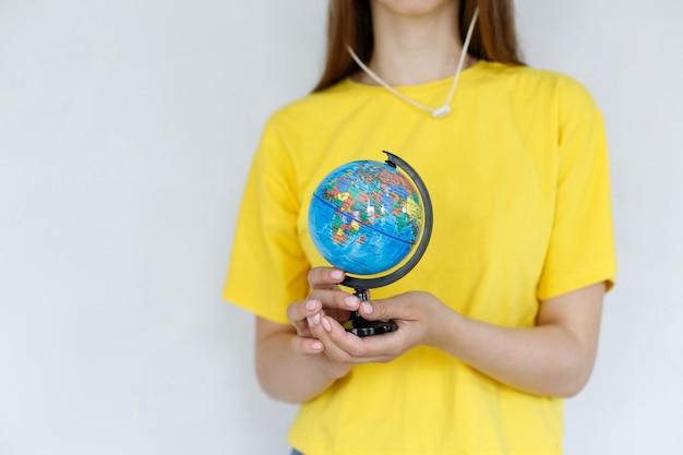 灰色の背景のクローズアップに地球儀と明るいtシャツの女の子