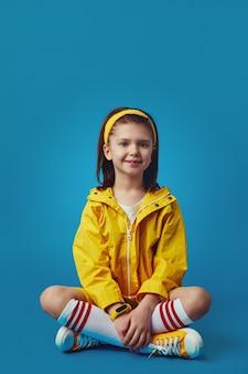 Девушка в ярко-желтом наряде улыбается в камеру, сидя со скрещенными ногами