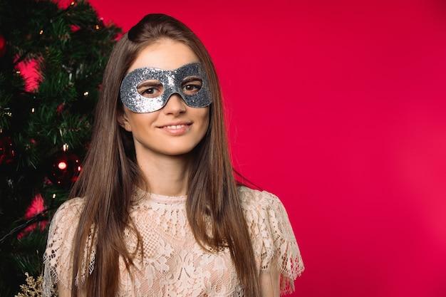 Девушка в карнавальной маске, праздничное настроение возле елки на красном фоне с пустым пространством