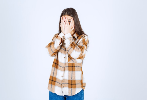 Девушка в повседневной одежде закрыла лицо анфас на белой стене.