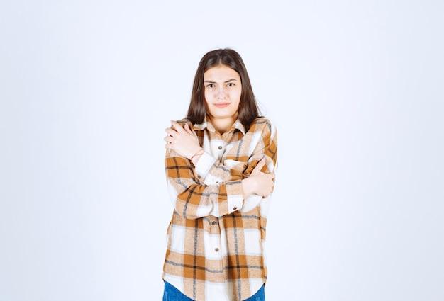 白い壁に寒さを感じるカジュアルな服装の女の子。