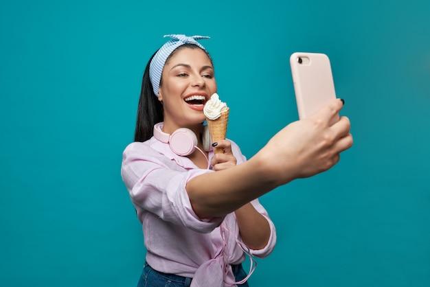 Selfieを取り、アイスクリームを食べるカジュアルな服装の女の子