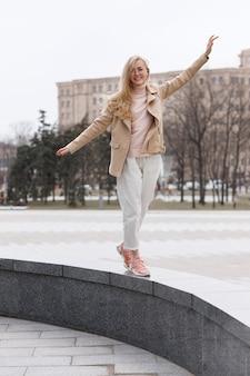 街を歩いて腕を上げてカジュアルな服を着た女の子