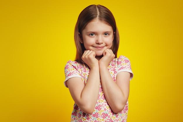 Девушка в повседневной рубашке держит руки на лице, изолированном на желтом фоне