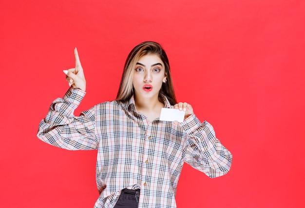 名刺を持って驚いたように見えるチェックシャツの女の子